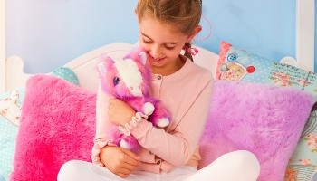 Little girl holding Pony Scruff-a-Luv © Moose Toys UK