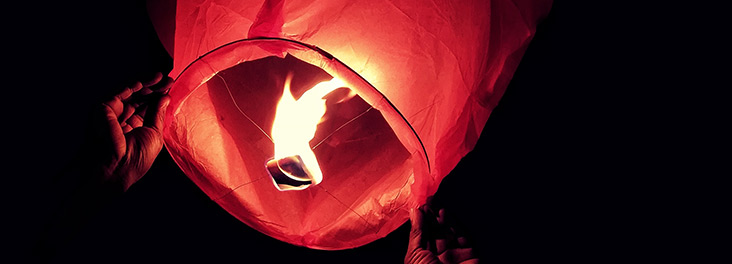 Sky lantern being released at night © Canva