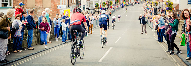 Cyclists on a road being cheered on
