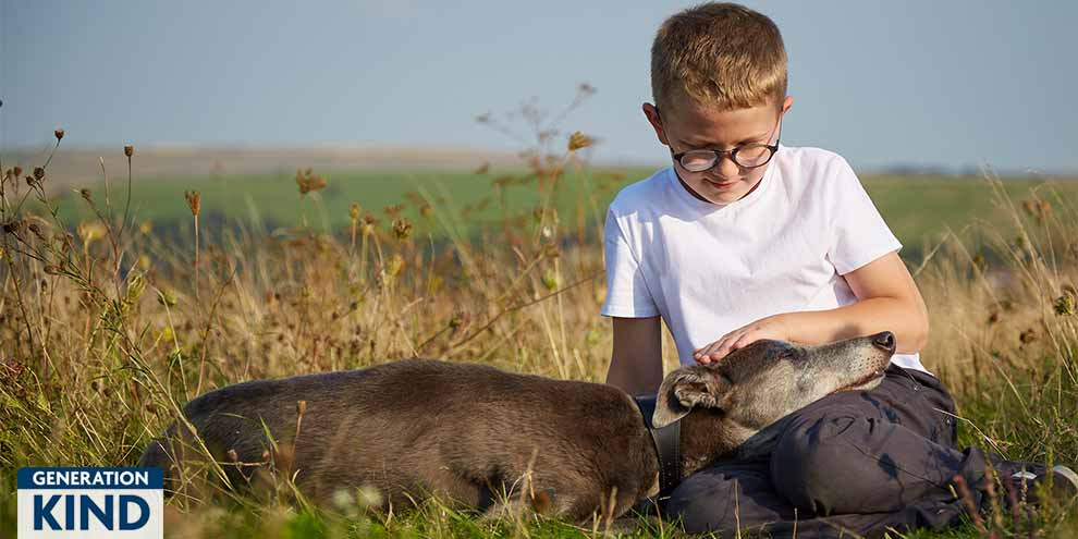 Boy sitting in a field with his greyhound  © RSPCA