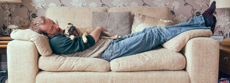 Man cuddled up with rehomed dog on the sofa © RSPCA photolibrary