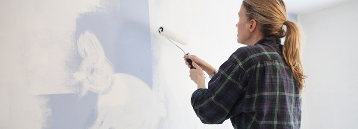 Woman painting wall with rabbit image © RSPCA photolibrary